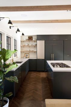 Modern transitional chef's kitchen with herringbone floors, blue black cabinets, white concrete countertops, exposed beams