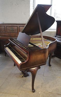 A 1940, Feurich Baby Grand Piano For Sale with a Walnut Case and Cabriole Legs at Besbrode Pianos. Piano has an eighty-eight note keyboard and two-pedal lyre.
