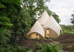 Teepee-shaped buildings by Issei Suma house community kitchen and pool