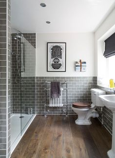Dark rustic wood floors, gray subway tile, glass walk-in shower and white…