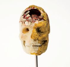 Kurt Cobain's Art.  Skull with a ruptured frontal bone, exposing the brain. The skull has been fleshed-out on one side with yellow modelling clay.