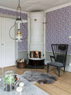 """1800-TALSHUS MED KAKELUGNAR I VARJE RUM: Det ljusa såpskurade furugolvet, den grå panelen och den vackra koboltblå tapeten skapar en rogivande känsla i vardagsrummet som har stora fönster med böljande munblåst glas. Intill vardagsrummet ligger sal och bibliotek i fil. Rummen är tapetserade med klassiska medaljongtapeter som andas 1800-tal. """"Vi valde att renovera ett rum i taget. Det var en grundlig renovering som skulle till, så det tog lång tid att få klart huset. Vi lyfte upp golven och…"""