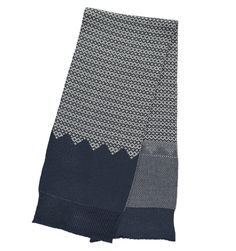 Miss Pom Pom Navy and Cream Reversible Graphic Knit Scarf: This Miss Pom Pom Reversible Graphic Knit Scarf in Navy Blue has a central panel that features a navy blue and white jacquard style knit. It is reversible; one side features an additional panel with smaller stitches in blue and white and; and the other has a contrasting pyramid style design. Both sides have chunky ribbed knit ends. This scarf has been lovingly made from 100% acrylic which is hypoallergenic and super soft. This scarf…