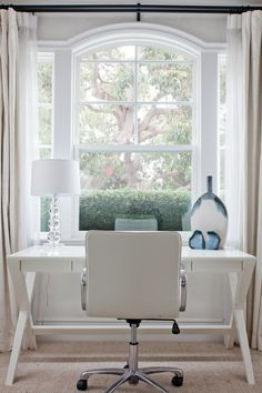 A small x-base desk occupies a little nook in this Newport Beach, Calif., home's spacious master suite. The white desk and matching white chair tie into the space's neutral palette.