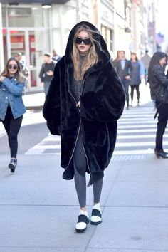 Hadid looked cozy hitting the streets of New York, topping her black + white athleisure look with an oversized furry coat.