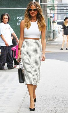 Chrissy Teigen is wearing a fitted white crop top, polka dot midi pencil skirt, and black accessories to finish off the clean look
