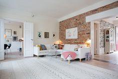 skandynawski salon,ściana z czerwonej cegły,biały salon ze ścianą z cegły,biala sofa w skandynawskim salonie,kolorowe poduszki na sofie,ozdobne poduszki w aranżacji wnętrz,biały dywan z etnicznym wzorem,grafiki na ścianach we wnetrzach,skandynawski styl w salonie,obraz nad sofą,sztuka we współczesnych wnętrzach