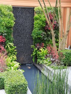 This vertical garden with a waterfall feature uses space efficiently and creates drama using lush flowers and foliage.