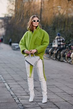 Copenhagen fashion week street style January 2019: a green jacket worn with white over-the-knee boots
