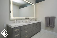 A large custom vanity with double sinks and a built in led mirror. Lots of storage in the vanity for with modern hardware.
