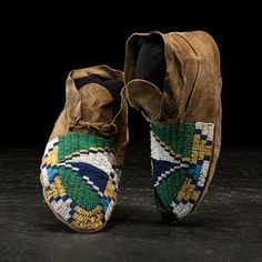Sioux Beaded Hide Moccasins thread and sinew-sewn with vamps fully beaded with geometric designs using colors of two shades of green, greasy yellow, white, dark blue, and light blue, length 9.5 in. fourth quarter 19th century Price Realized Including Buyer's Premium $840 04/08/2016 Price Realized Including Buyer's Premium $840 04/08/2016