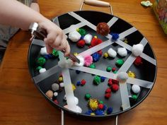 Sticky tape and pom poms fine motor skill developing activity in a Kmart play tray