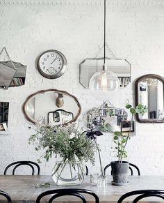 . grey white black mirrors vintage vases concrete lighting florals wood