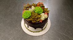 A tiny buttercream succulent garden graces the top of this ganache drizzled four inch cake.