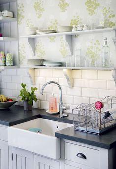 Astiat ovat esillä avohyllyissä. Grohen Eurosmart Cosmopolitan -yksiotehanassa on myös tiskikoneen hana samassa. Työtasot ovat pyökkiä, sävynä ardoise. Led-nauhavalot piilotettiin ylähyllyjen alapintaan. Arjen pienet käsitiskit kuivuvat porvoolaisesta Vanille Home -sisustusliikkeestä ostetussa Madam Stoltzin astiankuivaustelineessä.