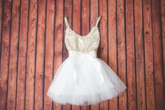 This dress is just beautiful! It includes a gold sequined bodice with gold elastic spaghetti straps and a white tulle tutu skirt. It also has