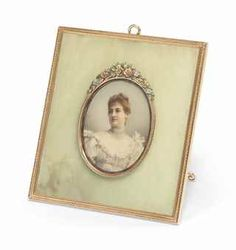 A FABERGÉ FOUR-COLOUR GOLD-MOUNTED BOWENITE PHOTOGRAPH FRAME, WORKMASTER MICHAEL PERCHIN, ST PETERSBURG, CIRCA 1890. Rectangular, the bowenite panel centring an oval aperture within a bright-cut gold border, enclosing a glazed portrait miniature on mammoth ivory of Princess Anastasia of Montenegro, surmounted by four-colour gold flower garland, all within a bright-cut chased gold outer border.