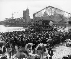 1900s A huge crowd fills the beach near the Venice Pier. A platform and stage can be seen at the base of the roller coaster.