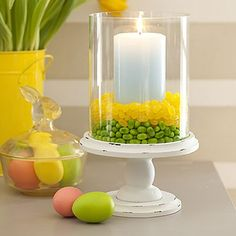 Sweeten a candle display - Use the abundance of jelly beans to bring some color to the table. Place a glass hurricane on a plate or pedestal. Center a pillar candle inside it. Fill the surrounding space 1 high with one color of jellybeans, then add a 1 layer of a different color directly on top.