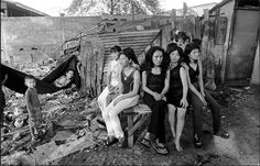 Women and children forced into sex trafficking in Cambodia in order to pay off their families debts await outside a brothel.