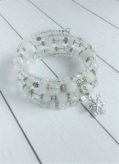 This dazzling white beaded bracelet starts with four strands of stainless steel memory wire which holds an assortment of crisp white beads with a few iridescent beads for a touch a sparkle. From seed beads to glass beads, every single bead has been hand selected for this bracelet.