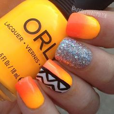 Silver glitter nail art with black and white tribal designs on top of a yellow and orange gradient nail art design.