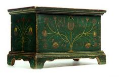 "FINE DECORATED MINIATURE BLANKET CHEST, Attributed to western Virginia, 2nd quarter-19th century, poplar. Dovetailed case on bracket feet, and retaining its original stylized flower decoration in red and gold, against a green ground. Minor imperfections. 11.25""h. 17.5""w. 9.75""d."