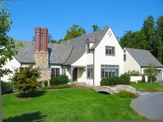 Several distinctive Tudor characteristics combine in this new home. Though it's labeled English cottage, the impressive stone and brick chimney illustrates a signature of many early grand Tudor examples.
