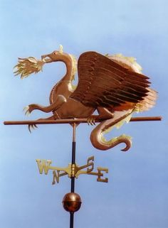 Dragon Weather Vane Fire Breathing Dragon by West Coast Weather Vanes.  The flames featured in this particular weathervane are made of alternating sheets of copper and brass and the horns, teeth, talons and spines have been optionally gilded with 23-carat gold leaf.
