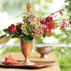 Glistening red currants create the framework for this asymmetrical bouquet, which is a wonderful example of how pretty flower-focused fall centerpieces can be. A pink-hue hydrangea bloom and a few red roses add interest to the angled line of the design./