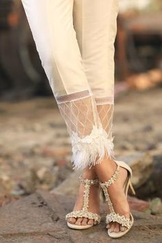 Ivory raw silk trousers with organza and feather lace styling on flare. Also available to order in black. Plazzo Pants, Salwar Pants, Sleeves Designs For Dresses, Moda Outfits, Salwar Designs, Straight Trousers, Pants Pattern, Indian Designer Wear, Pakistani Dresses