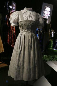 """The blue and white gingham pinafore dress worn by Judy Garland in her iconic role of Dorothy designed by Adrian for the 1939 film """"The Wizard Of Oz,"""" with a video portrait of Garland in the background, on display at the Hollywood Costume exhibition at the Victoria and Albert Museum in London, Tuesday, Oct. 16, 2012."""