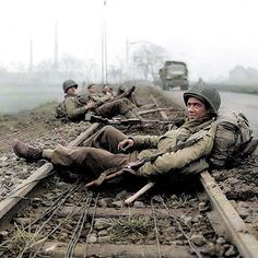 """the_ww2_archives GIs of the 413th Infantry Regiment, 104th Infantry Division """"Timberwolves"""", resting on the rail track after combat in Düren, a town in North Rhine-Westphalia, Germany. 21 December 1944. During the Battle of the Bulge, the 104th actively defended its sector near Düren and Merken from 15 December to 22 February 1945. (Colourised by Royston Leonard UK) https://www.facebook.com/pages/Colourized-pictures-of-the-world-wars-and-other-periods-in-time/182158581977012 2016/12/22…"""