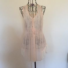 Sheer pink top Sheer light pink tank with lace detailing on chest and around bottom. Tie can be used to pull the top in at the waist or the ties can be let down for a wider fit to the top. Pics show it tied and let loose. Romeo & Juliet Couture Tops Blouses