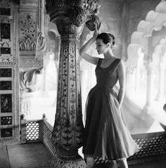 Norman Parkinson photographs Anne Gunning against Honeycomb marble carving of the Red Fort, Delhi, India, Vogue 1956. Anne Gunning wearing an evening dress in rose red chiffon by Susan Small.