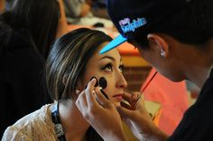 Priscilla Trujillo, 17, Harrison High School twelfth grader, receives a face painting of a panther paw from alumni Brandon Dines, a 2012 graduate, Aug. 25, during the Waldo Canyon Fire Relief Benefit Bash at Sand Creek High School in Falcon School District 49. Dozens of students from six area high schools coordinated the carnival-like fundraiser from 10 a.m. to 6 p.m. They raised roughly $3,000 for two local funds: Waldo Canyon Fire Victim Assistance Fund and the Waldo Canyon Fire Fighters…