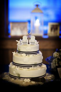 White wedding cake with navy and white striped ribbon trim.  Photo by Julie Dreelin's Beach Productions www.engagingeventsobx.com #engagingeventsobx #outerbankswedding