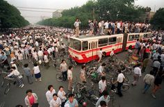 A huge crowd gathers at a Beijing intersection where residents used a bus as a roadblock to keep troops from advancing toward Tiananmen Square in this June 3, 1989 photo. (AP Photo/Jeff Widener) #