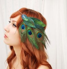 This wreath features layers of iridescent blue green leaves with three peacock feathers cascading at the side front...