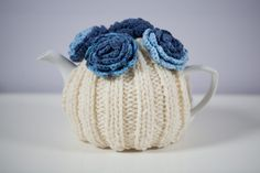 Cream coloured hand knitted tea cosy with crocheted flowers on top