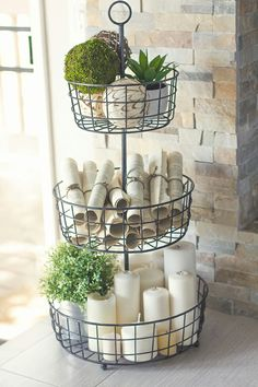 Love the mass of candles and the paper s rolls in the tiered basket w/touches of greenery