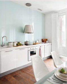 Светло-голубая стена и белая мебель на современной стильной кухне