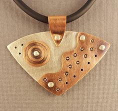 Modern yet retro! A handcut sterling silver rounded isosceles triangle is adorned by a copper handstamped layer and a simple circle of copper. The layers are cold connected by sterling silver rivets. The pendant is 1 7/8 long from the top of the sterling silver bail by 2 1/2 wide. The pendant hangs from a 4mm 18 rubber choker with a sterling silver lobster clasp. This pendant is signed Lisas Pieces. The pendant arrives boxed and ready for gift giving. Free First Class Shipping wi...