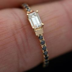 Made to Order Emerald Cut diamond engagement ring With Black diamonds on the band Center Stone .22ct emerald cut diamond G color SI2 clarity as seeing in the picture or can also be made with a .40ct. Center stone. 20 round brilliant cut Black Diamonds set Micro Pave on the shank 14kt