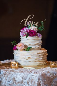 Ruffled cake with golden script topper and fresh flowers.