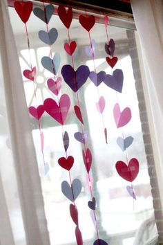 Make a heart garland for a Valentine's Day window! Great cutting and fine motor practice for preschoolers to cut out hearts and tape up together hearts!