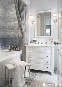 In a New York City bathroom designed by Sandra Nunnerley, mist mosaic tile by Studium has a watery, pearlescent glow. Vintage sconces from nicholas Antiques. Polished nickel fixtures and Easton stool by Waterworks. Towels by E. Braun & Co.