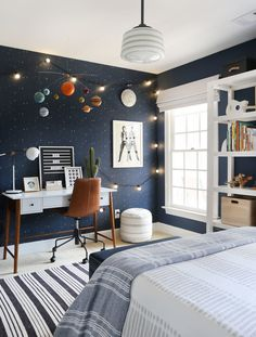 A bold, playful and out of this world kid's room | Sunny Circle Studio | Looking for boy's room ideas? This dark navy wall painted boys room with a star and solar system theme is perfect for the child curious and interested in space! #spacetheme #boysroom #kidsbedroom #navypaint