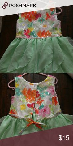 Girl's Special Occasion Dress 100% polyester. The top of dress features a colorful eyelet design over white shiny fabric. The back of dress is three buttons and tie. Emily West Dresses