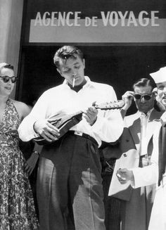 Robert Mitchum strums a mandolin while his wife Dorothy watches at the Voyage Agency in Nice, France